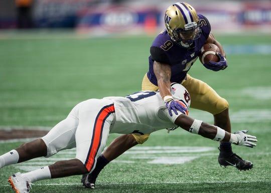 Washington's Myles Gaskin (9) is tackled by Auburn's Javaris Davis (13) at Mercedes-Benz Stadium in Atlanta, Ga., on Saturday, Sept. 1, 2018. Auburn leads Washington 15-13 at halftime.