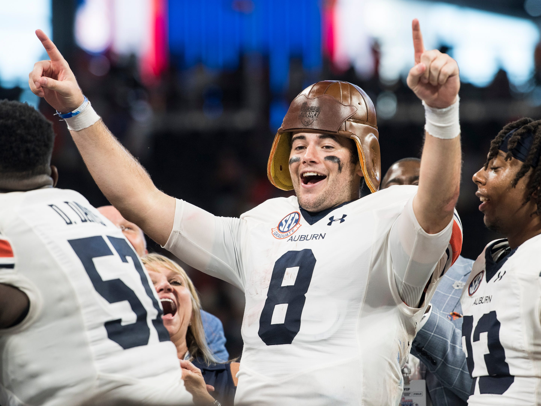 Auburn's Jarrett Stidham (8) wears the old leather helmet trophy at Mercedes-Benz Stadium in Atlanta, Ga., on Saturday, Sept. 1, 2018. Auburn defeated Washington 21-16 in the Chick-fil-a Kickoff Game.