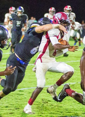 Montgomery Catholic's Charles Smith grabs Anniston's Tyree Carmichael from behind for a tackle.