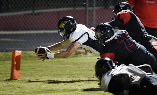 Giles County quarterback Bryce Wallace (12) dives into the end zone for a touchdown past the Pearl-Cohn defense during the game at Pearl-Cohn High School Friday, Aug. 31, 2018, in Nashville, Tenn.