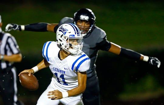 Lebanon quarterback Chandler Crite (11) runs from Mt. Juliet's Reggie Grimes during their game Friday, Aug. 31, 2018, in Mt. Juliet, Tenn.