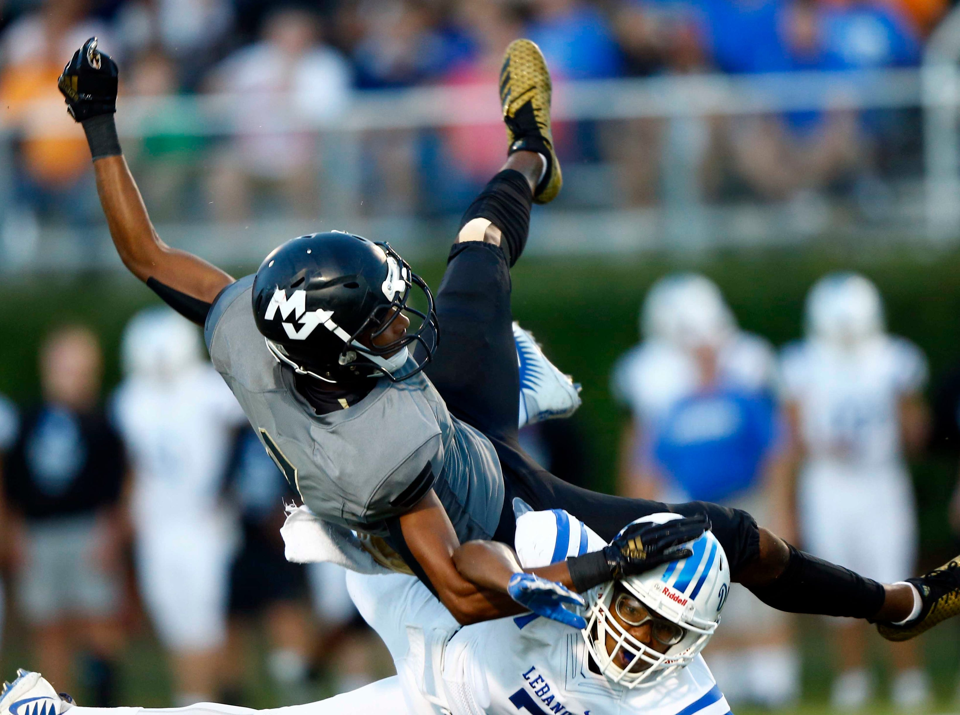 Mt. Juliet's Malik Bowen (3) is upended by Lebanon's Nathan Green during their game Friday, Aug. 31, 2018, in Mt. Juliet, Tenn. Bowen intercepted the ball on the play.