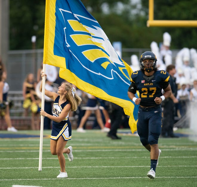 Naples cheerleader Lilly Herrera carries the school's flag onto the field as she runs with Chez Mellusi before the start of the game abasing Miami-Palmetto at Naples High Friday night, August 31, 2018.