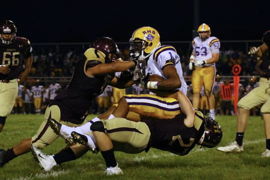 Raider standout Mershawn Rice (center) is tackled by the HornetsÕ Chris Townsend (left) and Marshawn Massey(right).The Hornets lost to the Raiders 44-0 on Friday, Aug. 31, 2018.