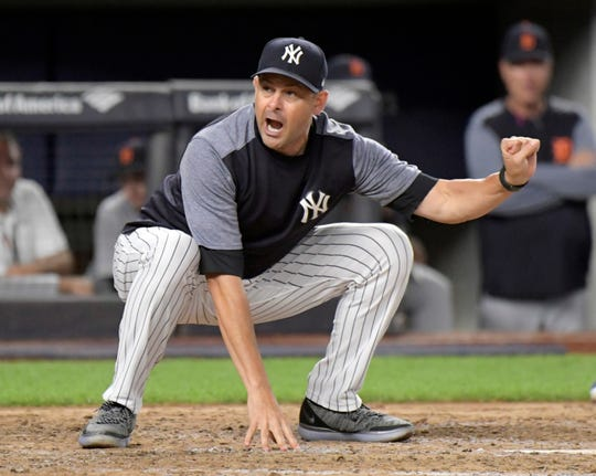 New York Yankees manager Aaron Boone demonstrates to home plate umpire Nic Lentz before being tossed from a baseball game against the Detroit Tigers during the fifth inning Friday, Aug. 31, 2018, at Yankee Stadium in New York.