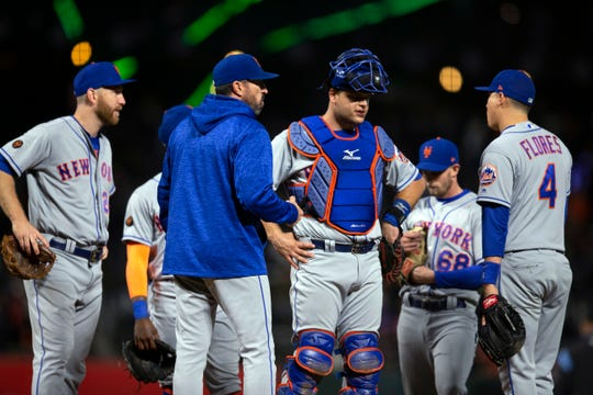 New York Mets manager Mickey Callaway, second from left, confers with his players during the eighth inning of a baseball game against the San Francisco Giants, Friday, Aug. 31, 2018, in San Francisco.