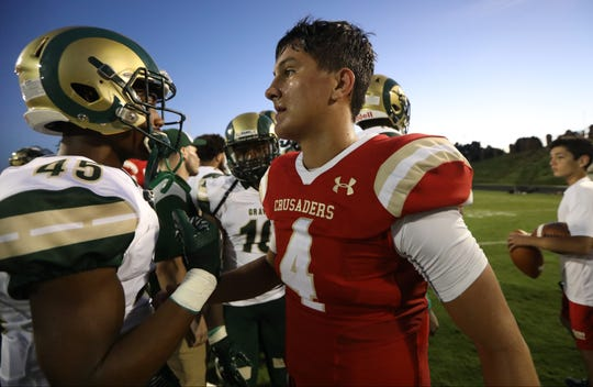 Bergen Catholic Quarterback, Andrew Boel, congratulates Jayoland Threat, of Grayson, GA. Friday, August 31, 2018