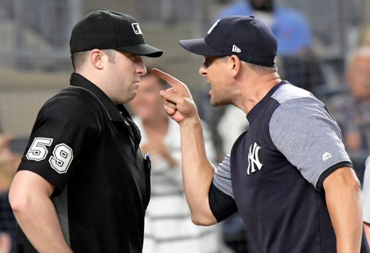 New York Yankees manager Aaron Boone, right, confronts umpire Nic Lentz (59) before being tossed from a baseball game against the Detroit Tigers during the fifth inning Friday, Aug. 31, 2018, at Yankee Stadium in New York.