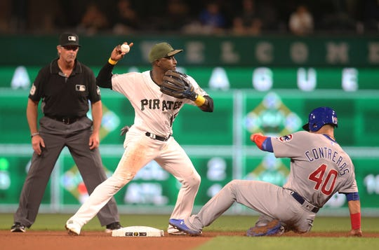 Aug 16, 2018; Pittsburgh, PA, USA; Pittsburgh Pirates shortstop Adeiny Hechavarria (15) throws to first base after forcing Chicago Cubs catcher Willson Contreras (40) out at second during the seventh inning at PNC Park.