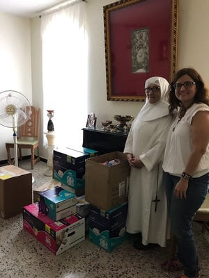 New Mexico State University assistant professor Ivelisse Torres Fernandez, right, delivered donations to an assisted living facility in Puerto Rico in July. Torres Fernandez, a native of Puerto Rico, has been a part of relief efforts to assist island residents still suffering from the effects of Hurricane Maria, which struck the island on Sept. 20, 2017.