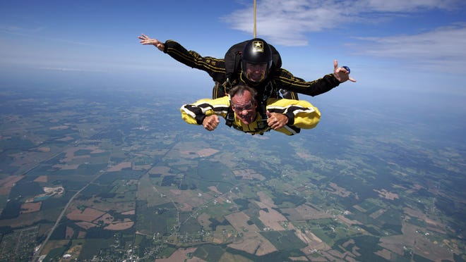 Dennis Giever, in yellow, head of New Mexico State University's Department of Criminal Justice, sky-dives with the Army Golden Knights.