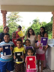 A group of students in Puerto Rico pose for a photo with New Mexico State University assistant professor Ivelisse Torres Fernandez while holding school supplies donated by the Las Cruces and NMSU communities. Torres Fernandez, a native of Puerto Rico, has made three trips to the island since Hurricane Maria devastated Puerto Rico and its residents in September 2017.