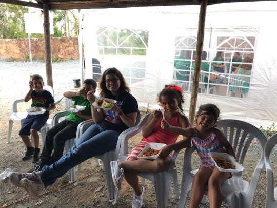 Ivelisse Torres Fernandez, an assistant professor at New Mexico State University, eats lunch with a group of students in Puerto Rico after delivering donations of school supplies. Torres Fernandez, a native of Puerto Rico, is researching the mental health of aid workers who helped Puerto Rican residents during Hurricane Maria in September 2017.