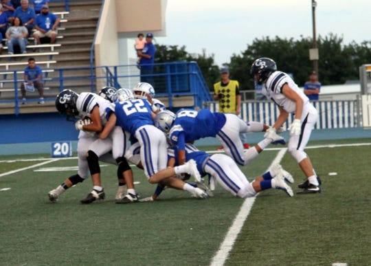 The Carlsbad defense gang tackles Goddard running back Robert Aragon in the first drive of Friday's game.