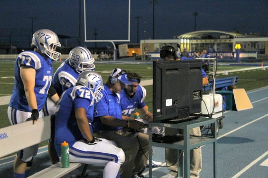 The Carlsbad line goes over footage with a coach during a break in Friday's game against Goddard.