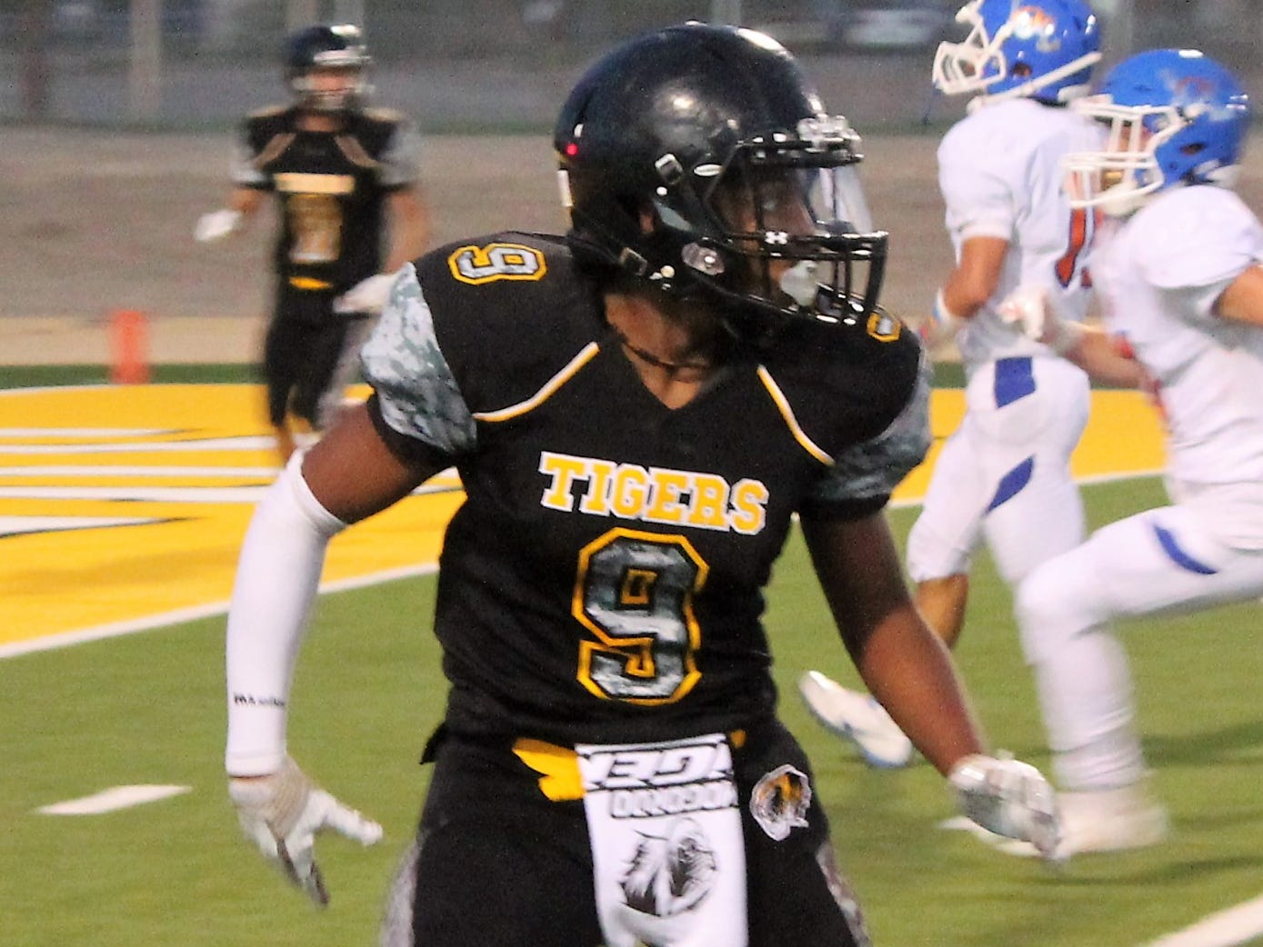 Alamogordo Tigers running back Jay Prude eyes the ball as he runs during the Tigers' games against Los Lunas Friday night.