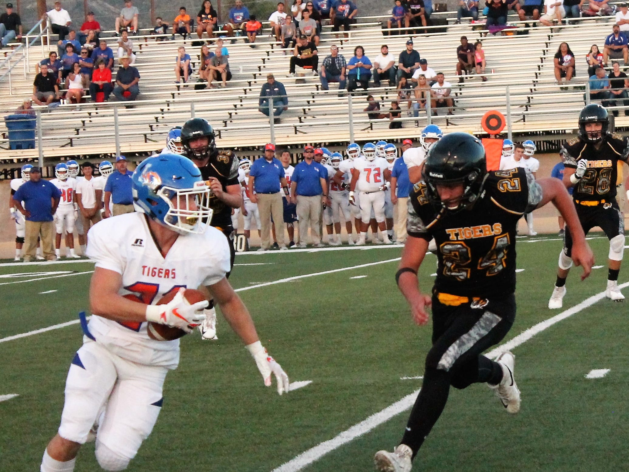 Alamogordo Tigers running back Mark Prather attempts an interception at Friday night's game against Los Lunas.