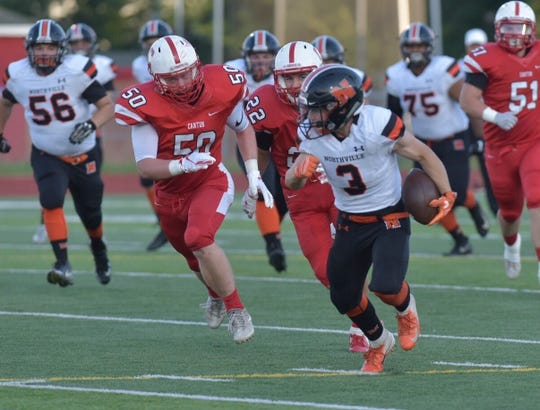 Breaking off a long gainer for Northville during the first half is senior Nicholas Prystash (3).