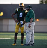 Farmington Hills Harrison head coach John Herrignton gives a play to QB Max Martin during week 2 action against Troy Athens.