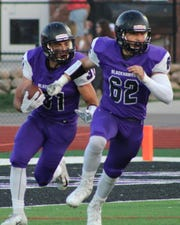Bloomfield Hills running back Austin Mehrman (21) is escorted down the field by lineman Park Haisha (62).