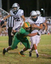 Eric Recio of Coachella Valley High stops La Quinta quarterback Jacob Calderon behind the line of scrimmage.