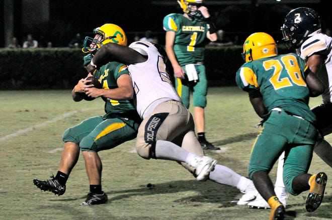 Gulf Breeze junior defensive lineman Tyrese Smith, who moved from Mississippi during the summer, tackles Catholic running back Seth Wilson for a three-yard loss as Pensacola Catholic threatened late in the fourth quarter. Gulf Breeze won the game 38-21.