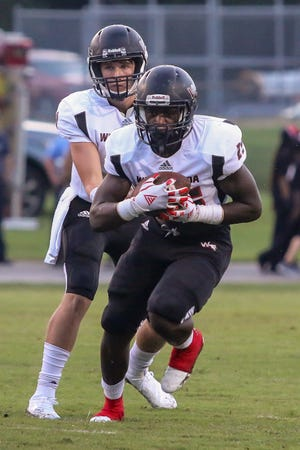 West Florida's Jaheim Simmons (25) runs the ball up the middle of the field against the Aggies at Tate High School on Friday, August 31, 2018.