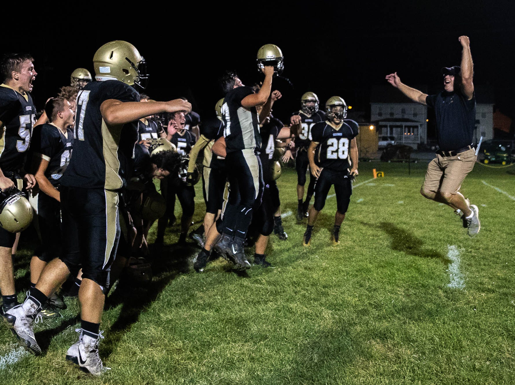 Delone Catholic defensive coordinator Dave Staub leaps into the air with his team after winning a game against York Suburban, Friday, Aug. 31, 2018, at Delone Catholic High School in McSherrystown. Delone beat York Suburban 62-0.