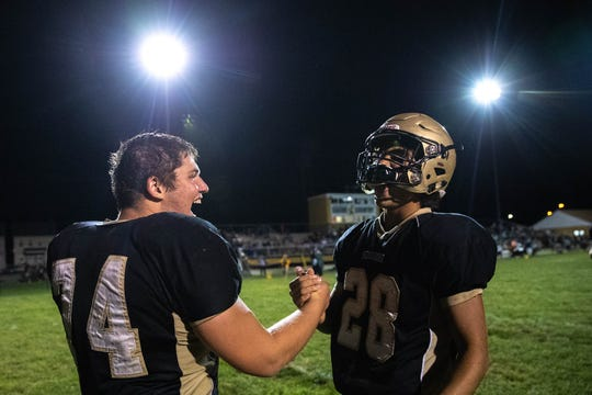 Delone's Zachary Groft (74) and Delone's Joe Hernandez (28) celebrate after winning a game against York Suburban, Friday, Aug. 31, 2018, at Delone Catholic High School in McSherrystown. Delone beat York Suburban 62-0.