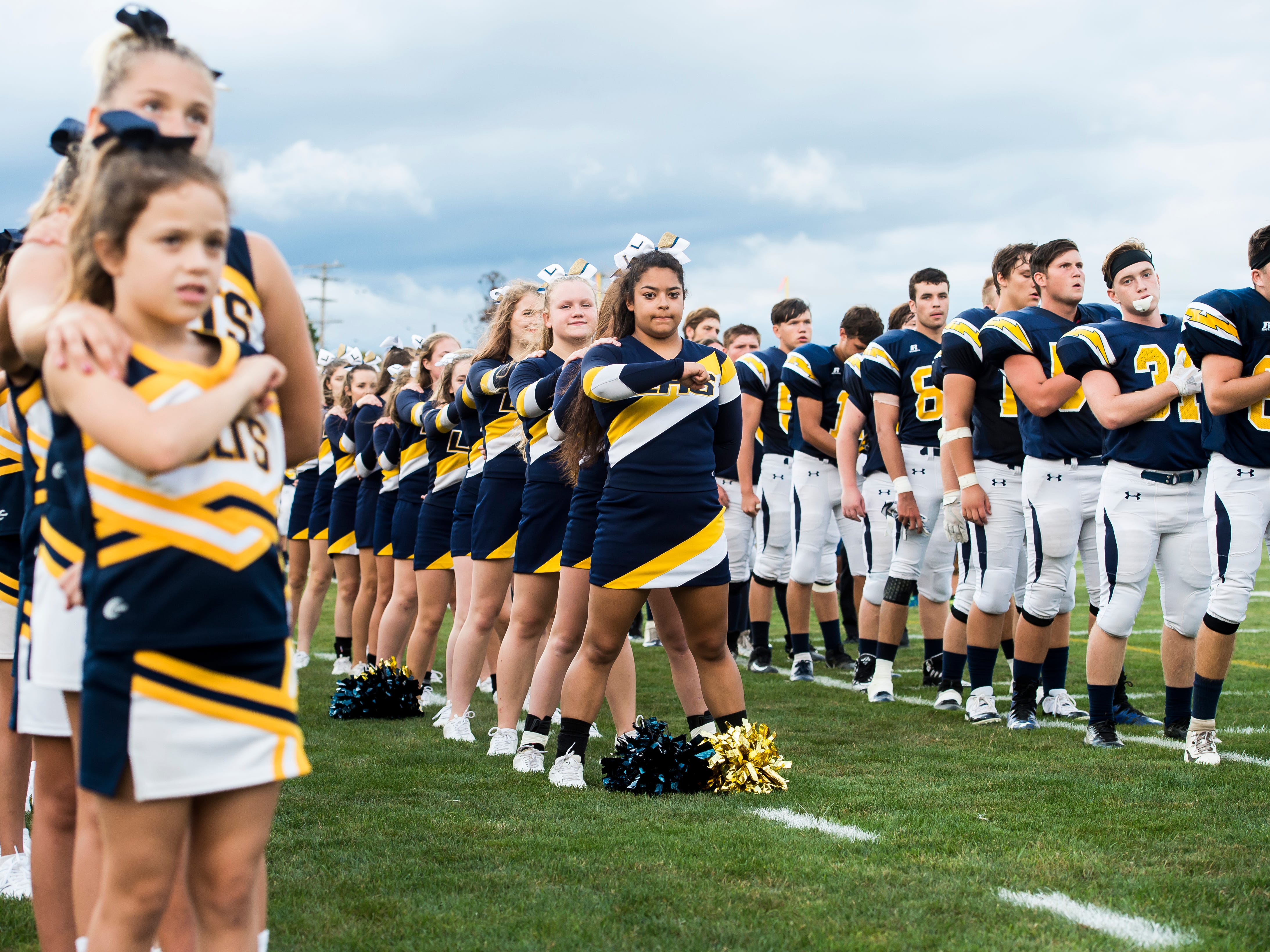 Littlestown cheerleaders and football players face the flag during the playing of the national anthem prior to Friday's game against Susquehanock. The Bolts beat the Warriors 29-14.