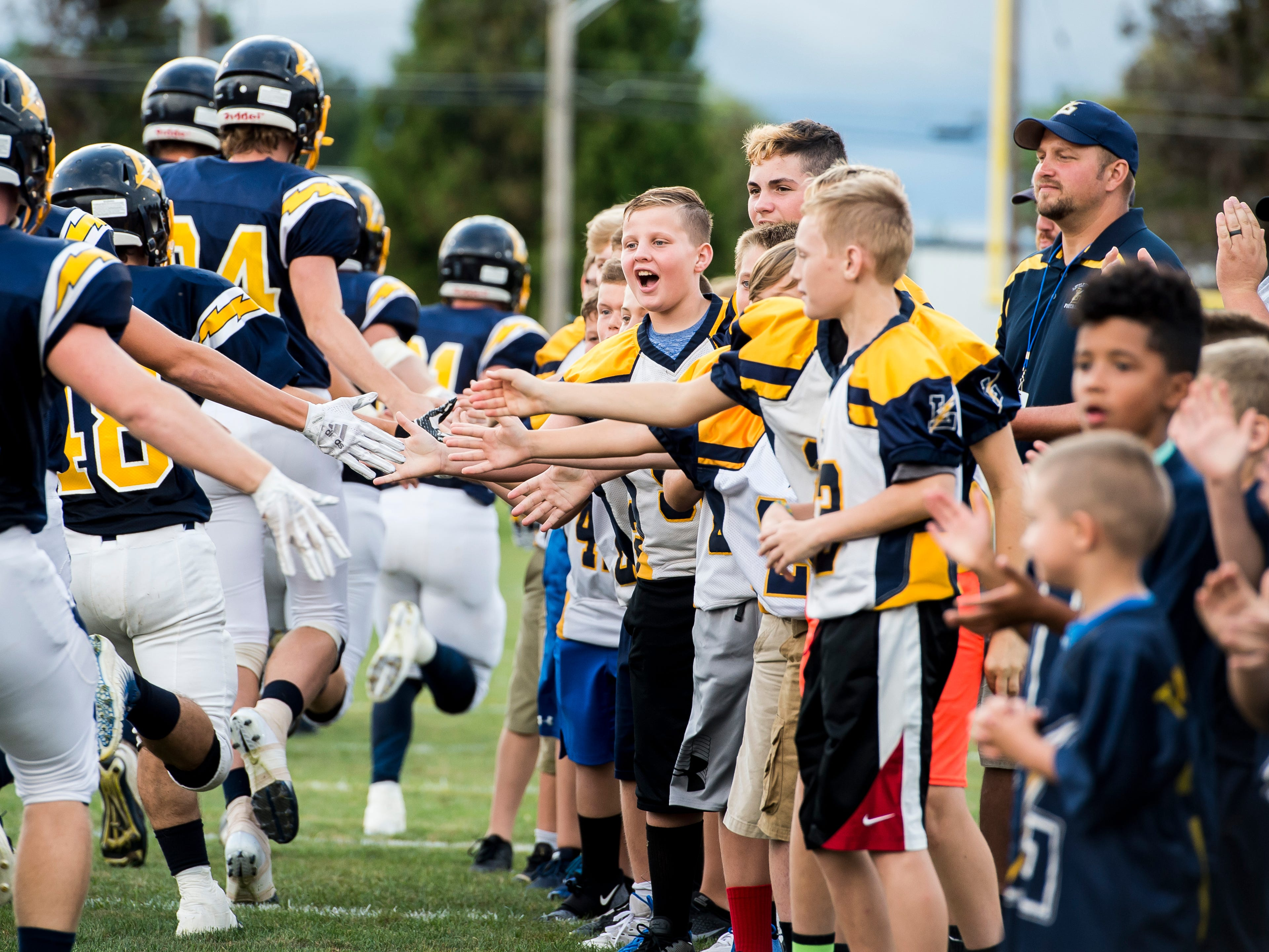 Littlestown fans high-five players as they run onto the field Friday, August 31, 2018. The Bolts beat the Warriors 29-14.
