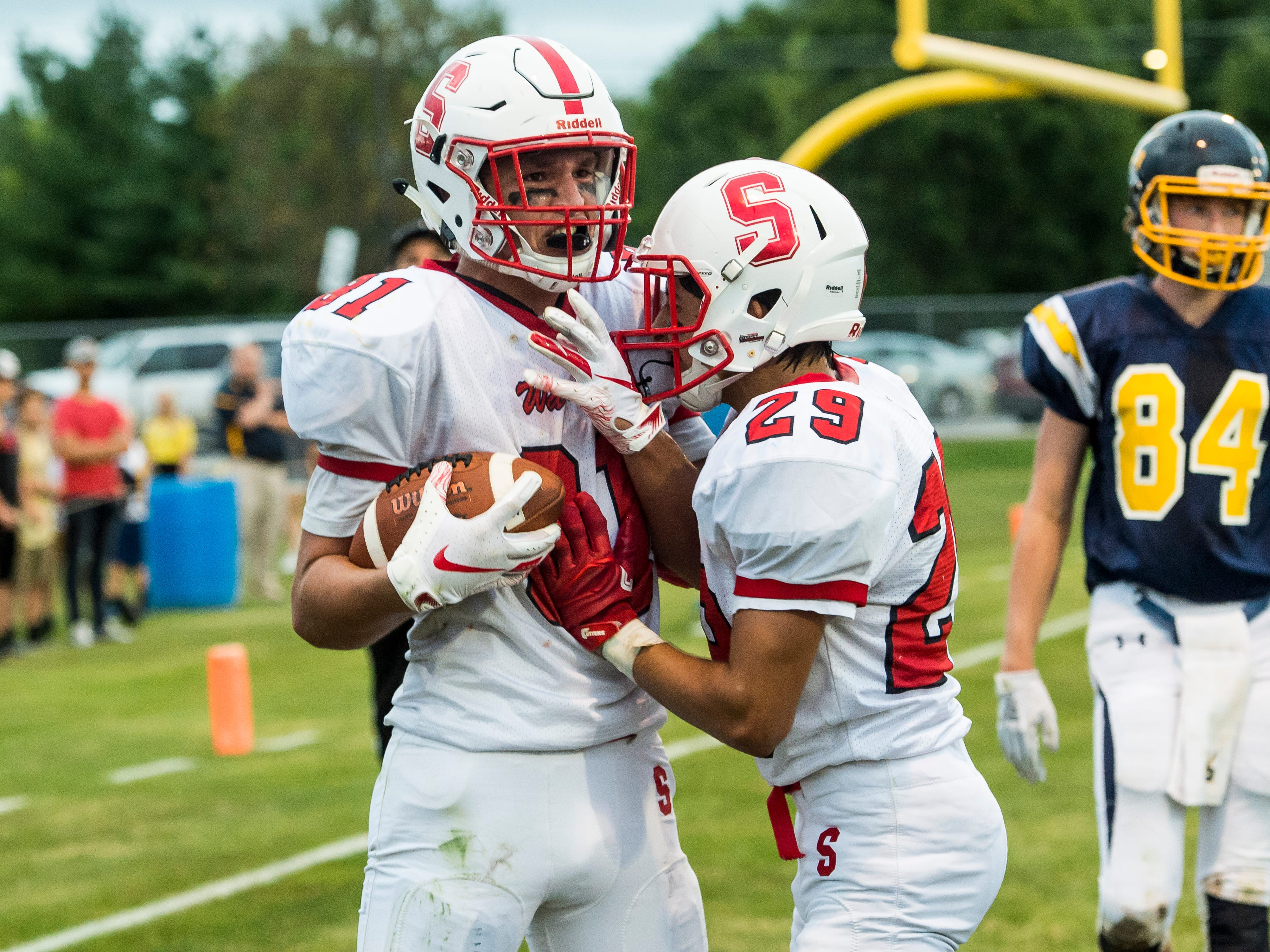 Susquehannock's Zach Green celebrates with teammate Harry Pecunes (29) after scoring a touchdown against Littlestown on Friday, August 31, 2018. The Warriors fell to the Bolts 29-14.