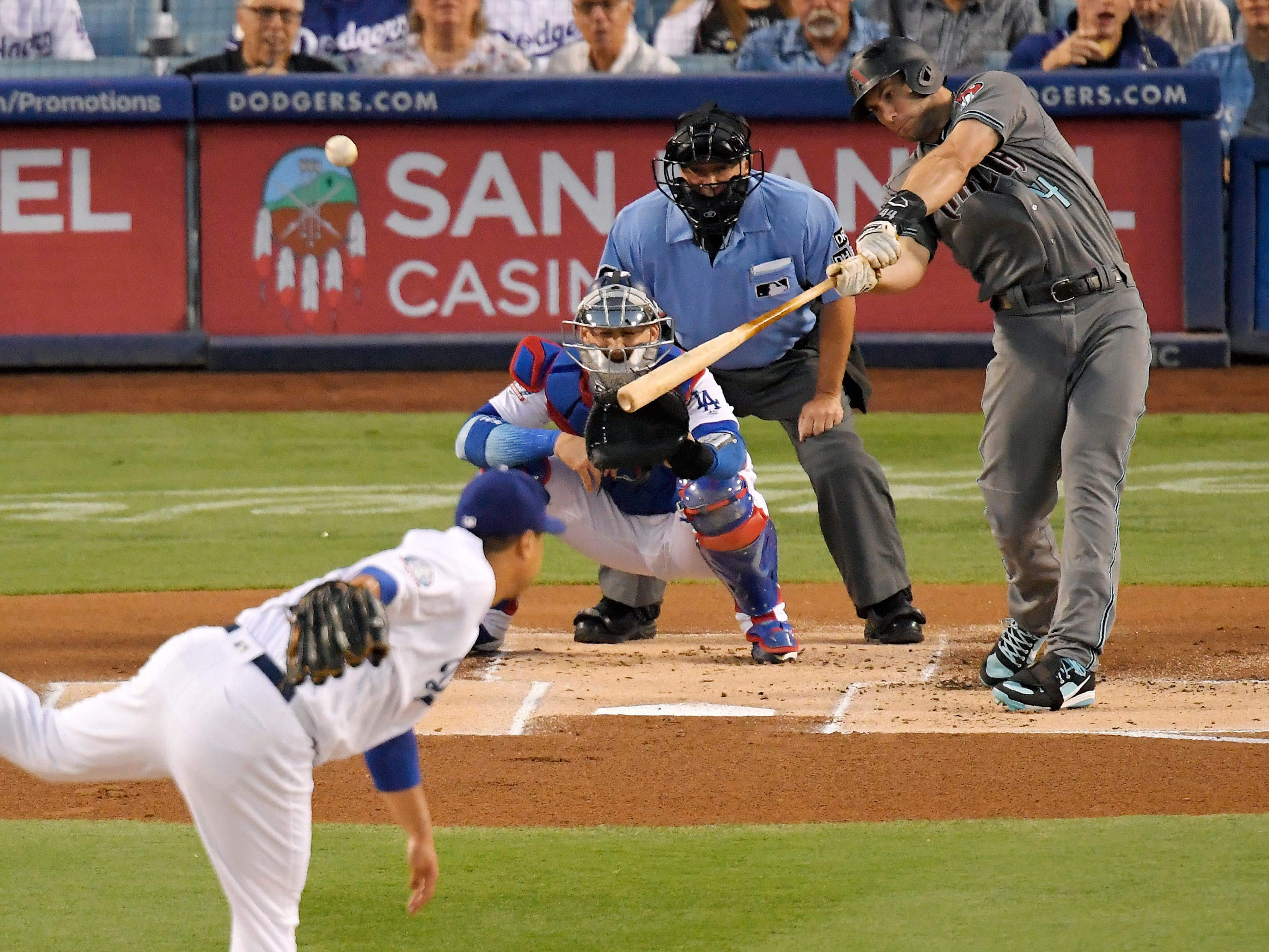Arizona Diamondbacks' Paul Goldschmidt, right, hits a two-run home run as Los Angeles Dodgers starting pitcher Hyun-Jin Ryu, left, watches with catcher Yasmani Grandal, second from left, and home plate umpire Tom Hallion during the first inning of a baseball game Friday, Aug. 31, 2018, in Los Angeles.