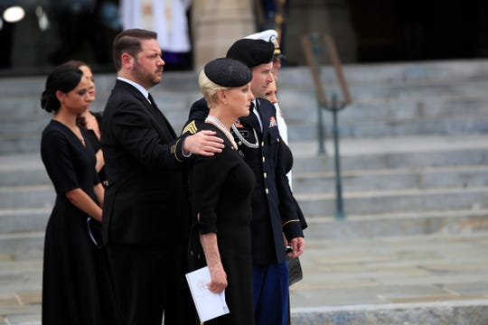 Jimmy McCain puts his arm around his mother Cindy McCain, and as other family members watch as McCain's casket is taken from the cathedral following a memorial service for Sen. John McCain at the Washington National Cathedral in Washington, Sept. 1, 2018.
