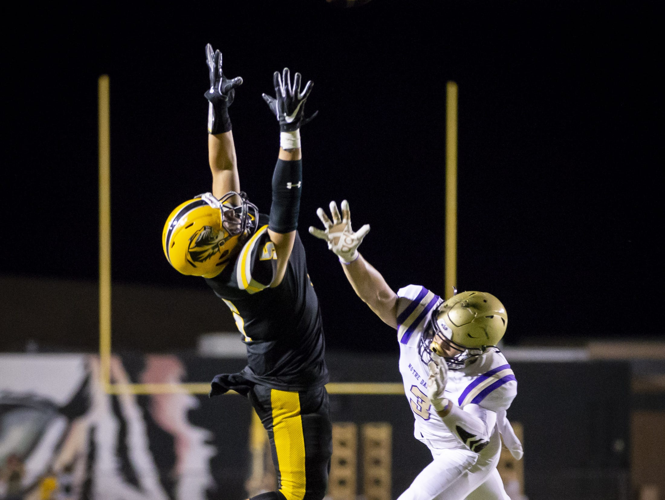 Junior running back Briggs Dupree (5) of the Gilbert Tigers attempts a catch against junior defensive back Connor Butt (3) of the Notre Dame Prep Saints at Gilbert High School on Friday, August 31, 2018 in Gilbert, Arizona.