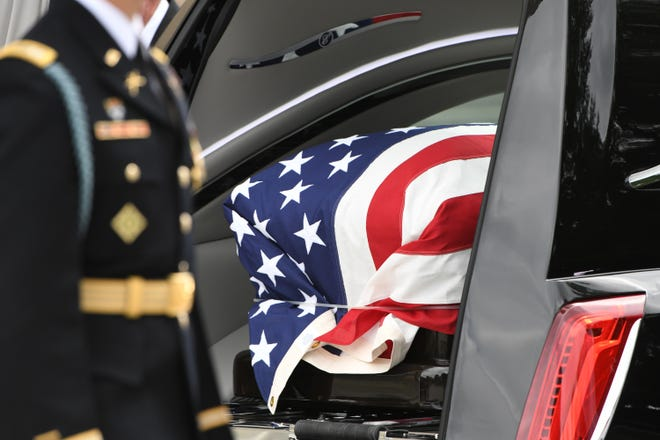 The flag-draped casket bearing John McCain is prepared to leave the National Cathedral in Washington on Sept. 1, 2018.