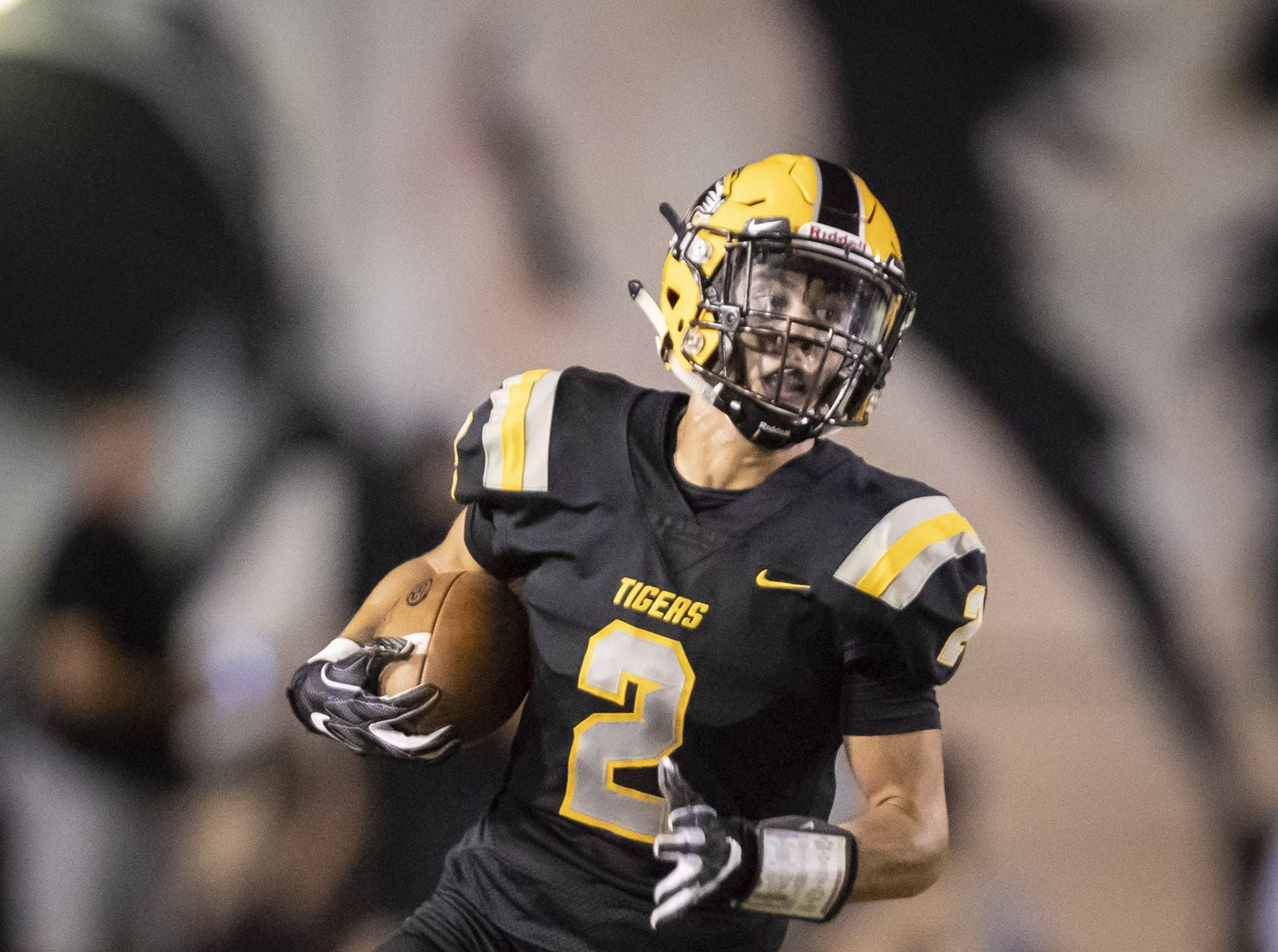 Junior wide receiver Tyler Hironaka (2) of the Gilbert Tigers runs the ball against the Notre Dame Prep Saints at Gilbert High School on Friday, August 31, 2018 in Gilbert, Arizona.