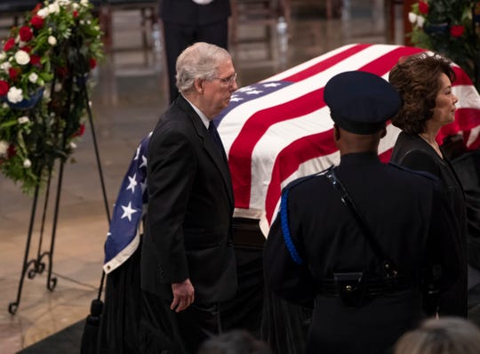 Senate Majority Leader Mitch McConnell, R-Ky., center, and his wife, Transportation Secretary Elaine Chao, pass Sen. John McCain's flag-draped casket on Friday, Aug. 31, 2018, in the U.S. Capitol rotunda in Washington.