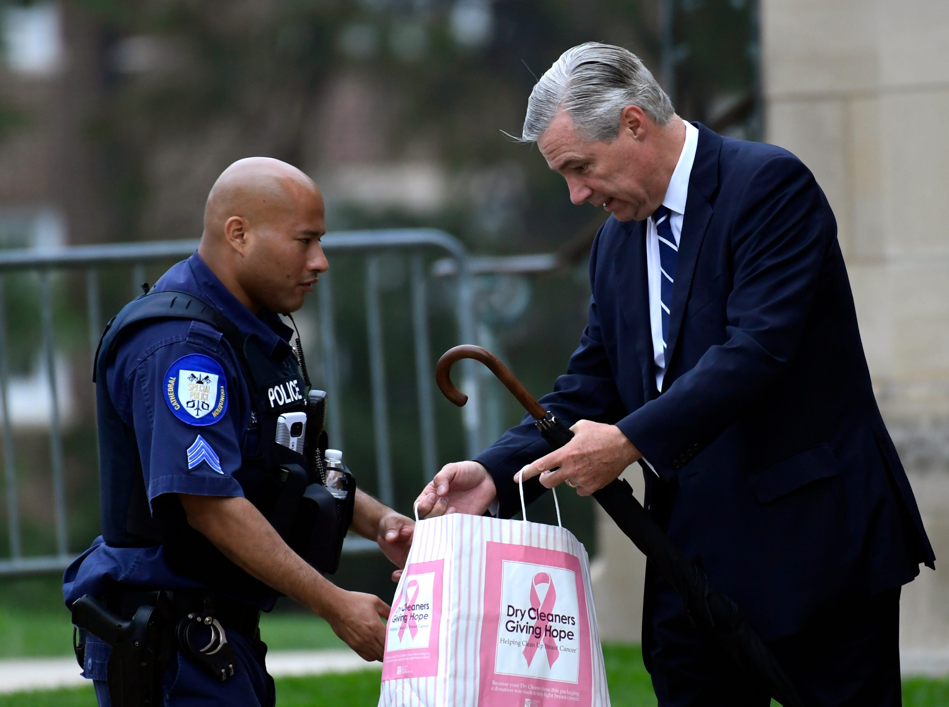 Sen. Sheldon Whitehouse, D-R.I., right, goes through security as he arrives to attend a memorial service for Sen. John McCain, R-Ariz., at the Washington National Cathedral in Washington, Saturday, Sept. 1, 2018. McCain died Aug. 25 from brain cancer at age 81. (AP Photo/Susan Walsh)