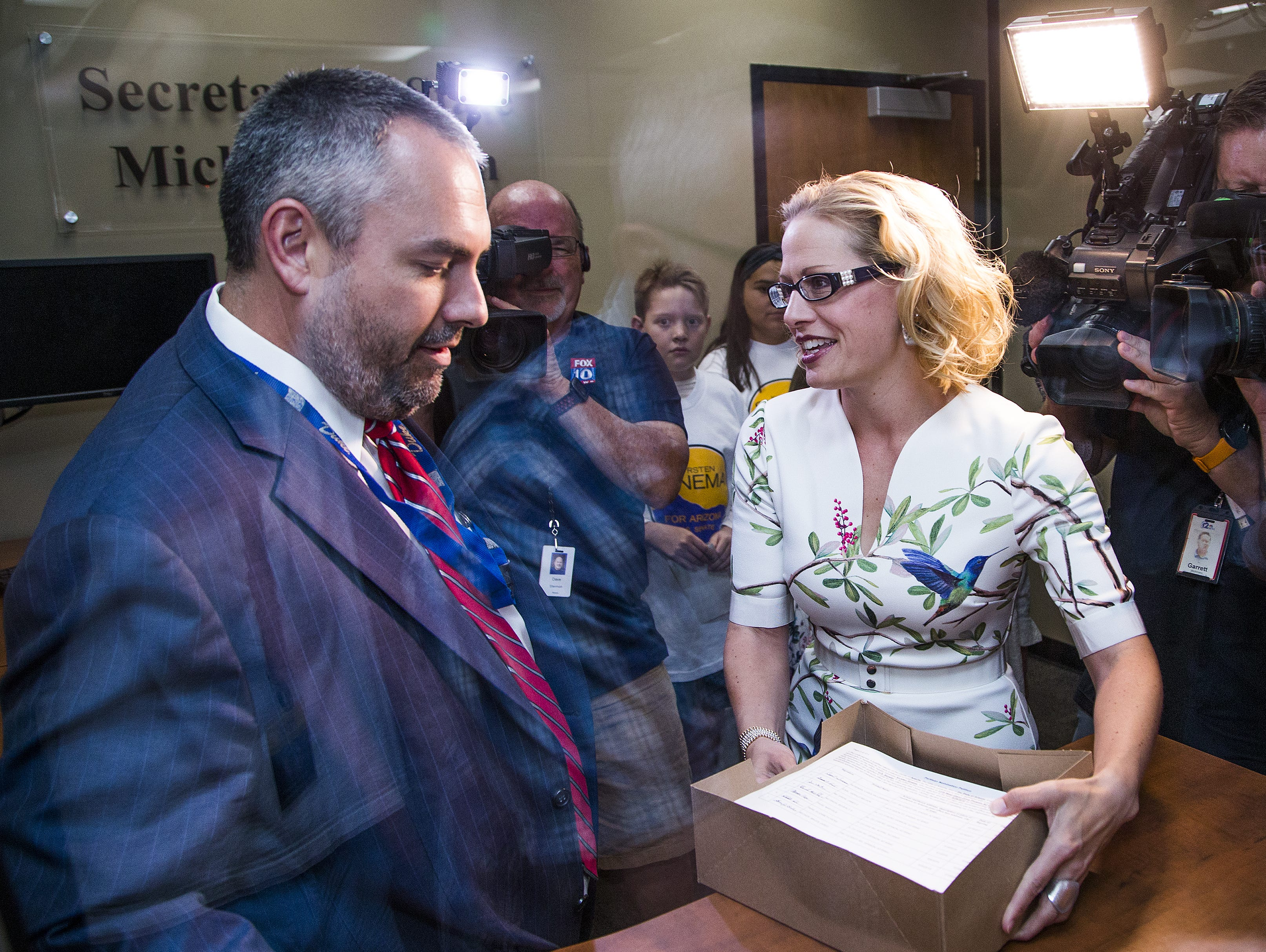 Rep. Kyrsten Sinema, D-Dist. 9, turns in signatures to Eric Spencer, director of election services for the Office of the Secretary of State, in Phoenix, Tuesday, May 29, 2018.   Sinema is running for U.S. Senate.