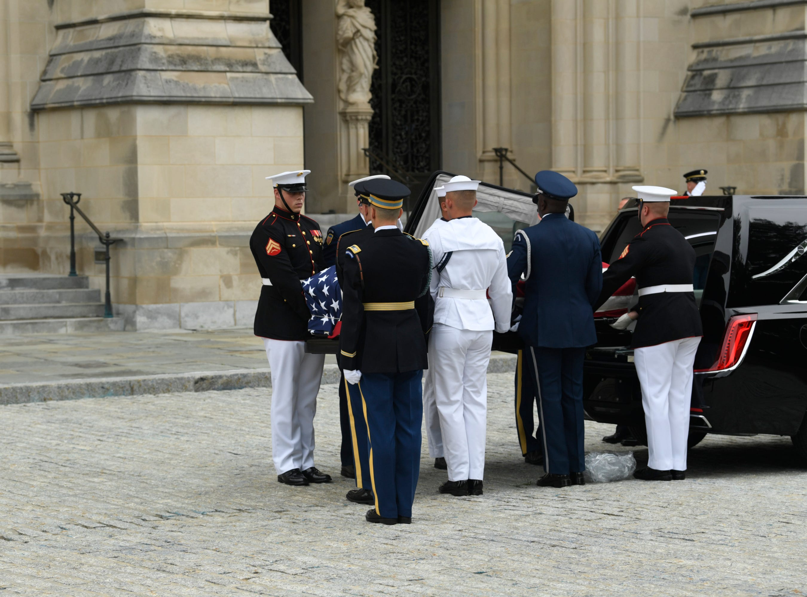 9/1/18 9:43:22 AM -- Washington, DC, U.S.A  -- A piece of plastic falls to the ground as the flag-draped casket bearing John McCain is carried into the National Cathedral in Washington for a memorial service on Sept. 1, 2018. Sen. McCain died on Aug. 25 --    Photo by Jasper Colt, USA TODAY Staff