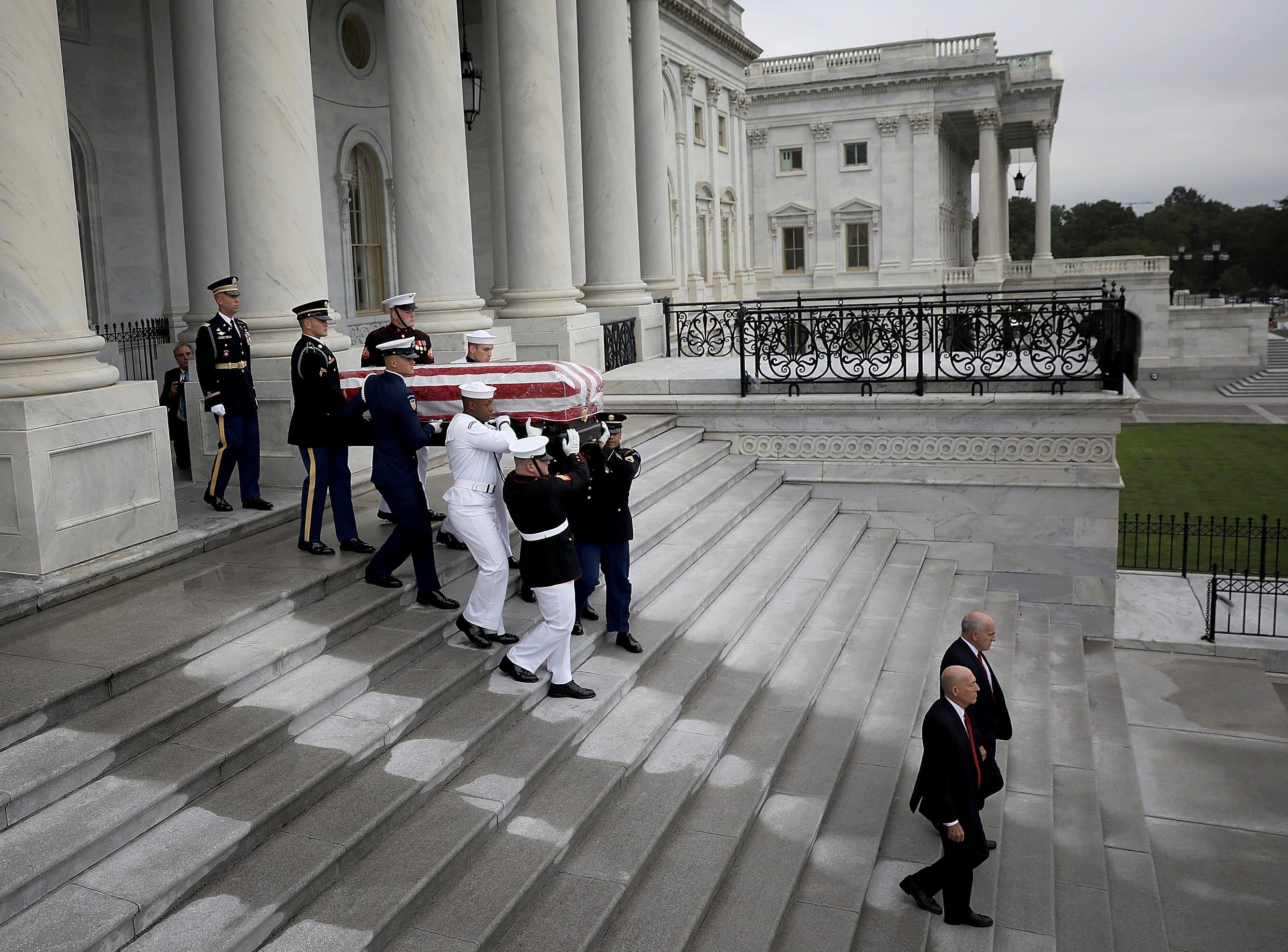 A military honor guard team carries the casket of Sen. John McCain, R-Ariz., from the U.S. Capitol, Saturday, Sept. 1, 2018 in Washington.  (Win McNamee/Pool photo via AP)
