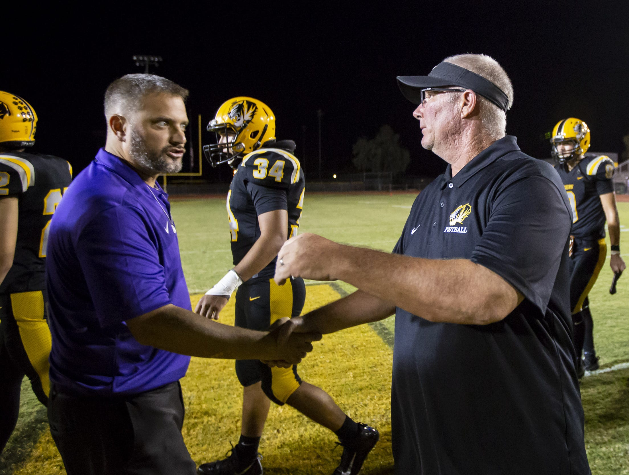 Head coach George Prelock of the Notre Dame Prep Saints (L) and head coach Derek Zellner of the Gilbert Tigers (R) shake hands following the game at Gilbert High School on Friday, Aug. 31, 2018 in Gilbert, Arizona.