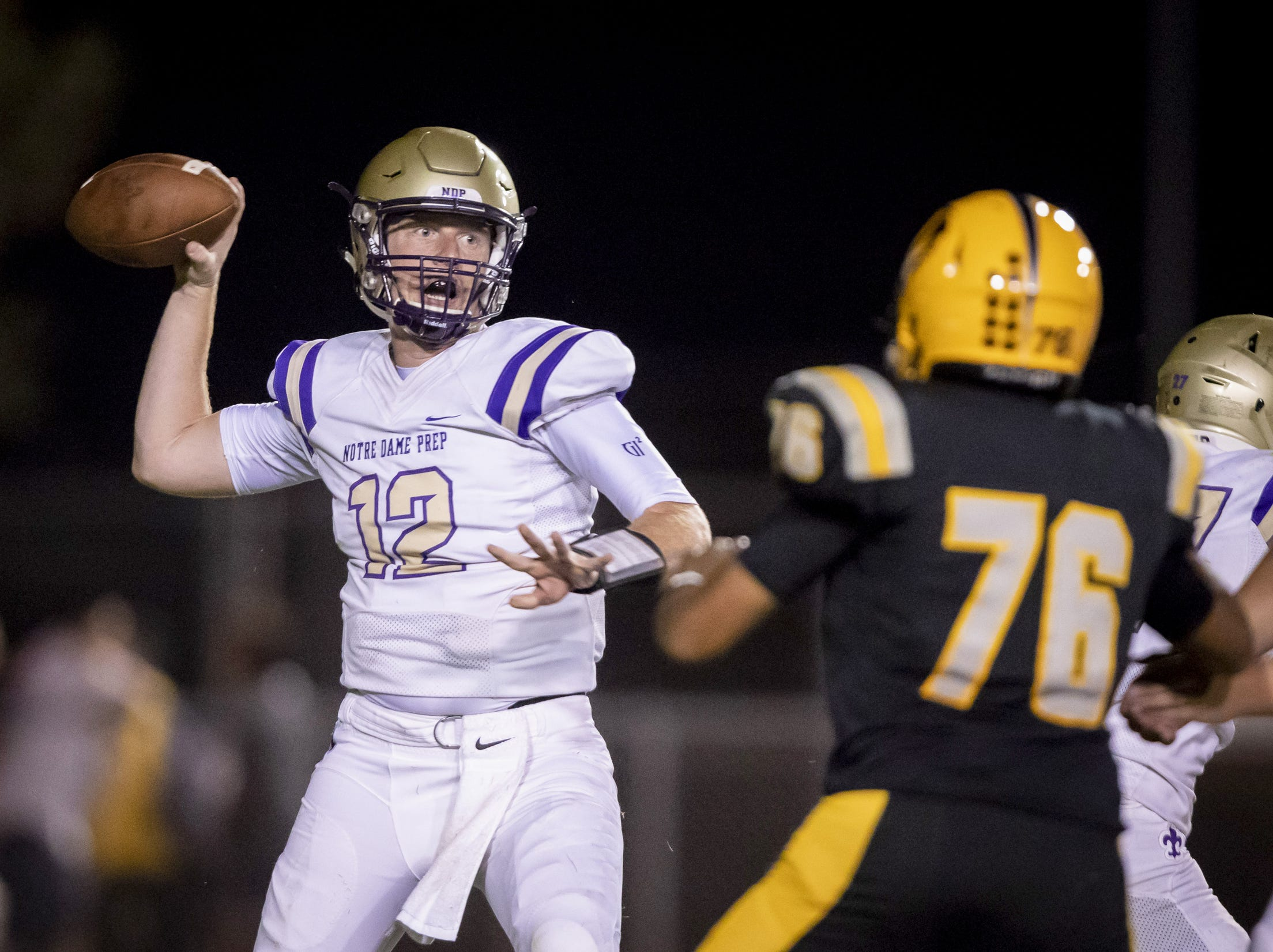 Senior quarterback Jake Farrell (12) of the Notre Dame Prep Saints throws a pass against the Gilbert Tigers at Gilbert High School on Friday, August 31, 2018 in Gilbert, Arizona.