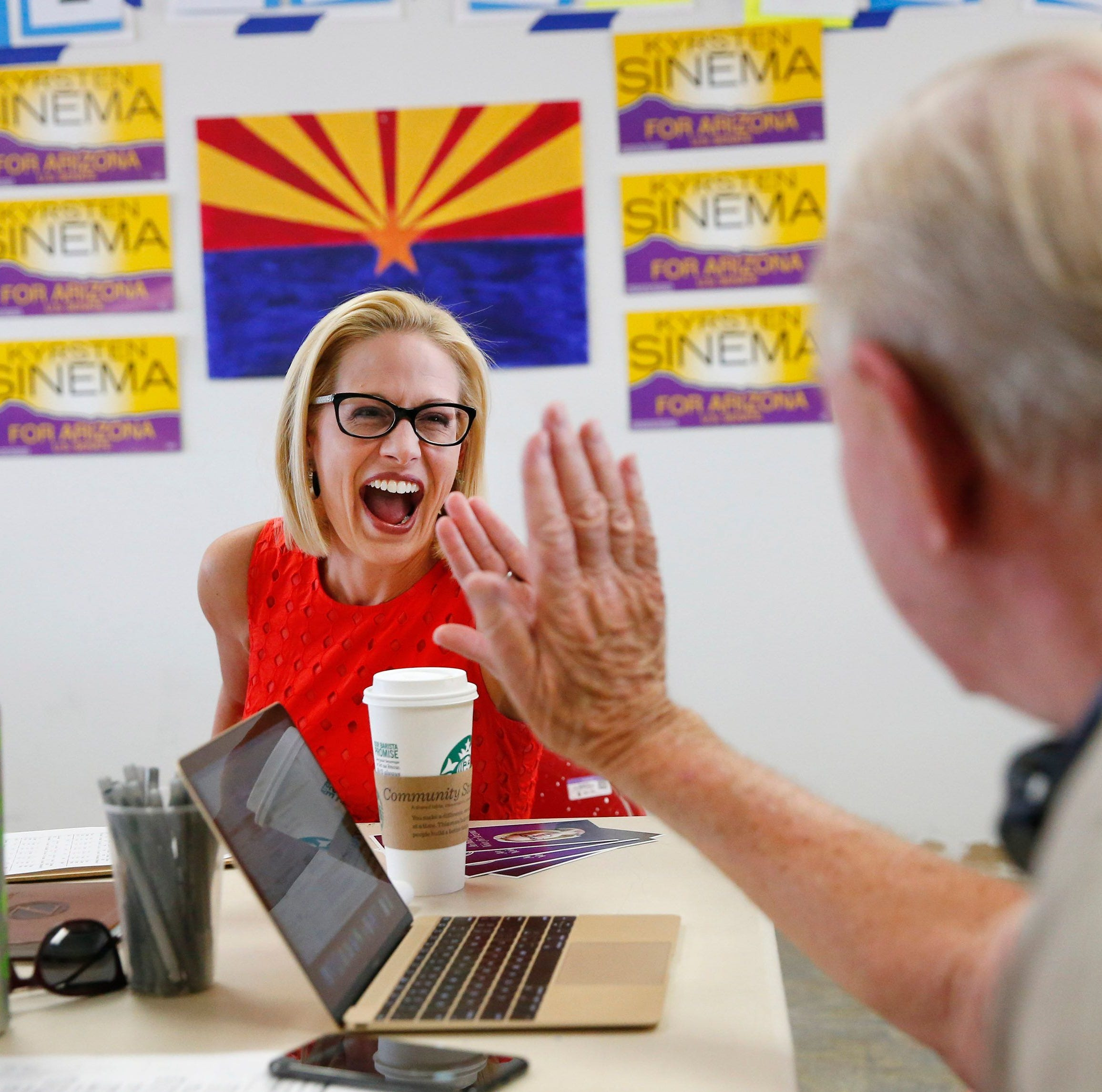 U.S. Rep. Kyrsten Sinema high-fives volunteer Bob Miller in Phoenix Tuesday. U.S. Rep. Kyrsten Sinema high-fives volunteer Bob Miller at her field office in Phoenix Aug. 28. 2018. Sinema is vying for the Democratic nomination for the open U.S. Senate seat.