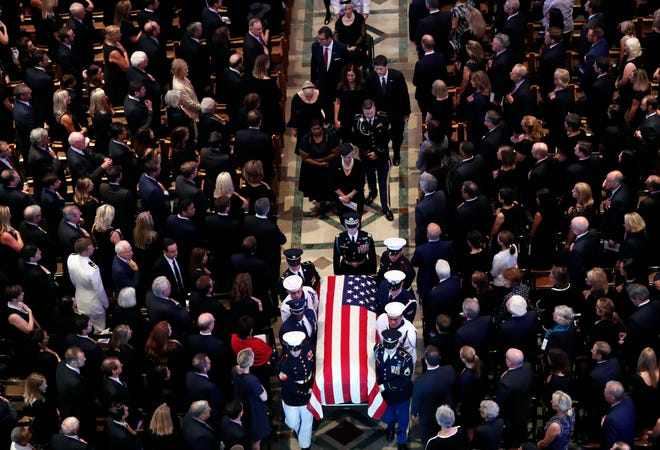 The family of Sen. John McCain, R-Ariz., follows as his casket is carried during the recessional at the end of a memorial service at Washington National Cathedral in Washington Sept. 1, 2018.