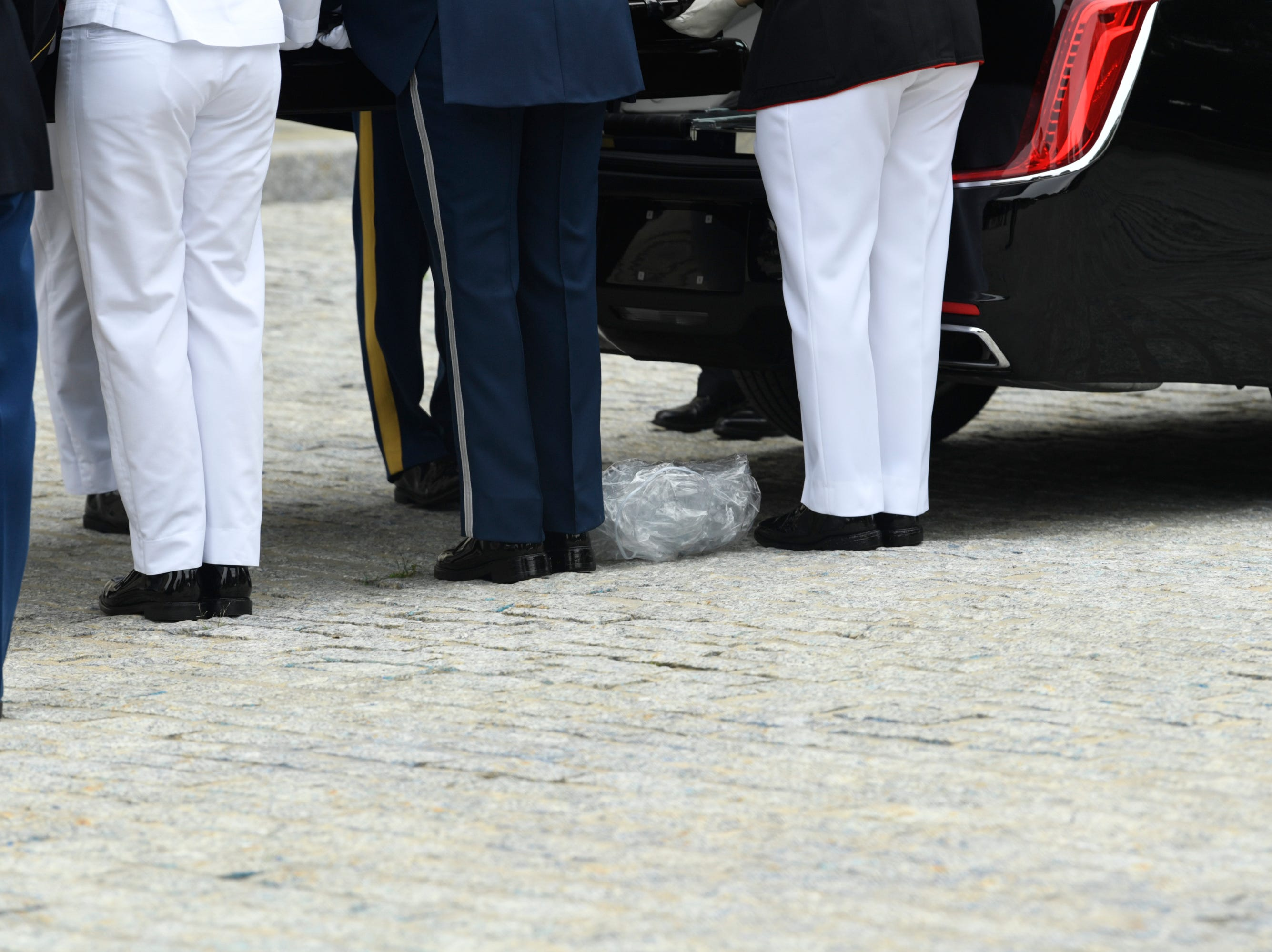 9/1/18 9:43:14 AM -- Washington, DC, U.S.A  -- A piece of plastic falls to the ground as the flag-draped casket bearing John McCain is carried into the National Cathedral in Washington for a memorial service on Sept. 1, 2018. Sen. McCain died on Aug. 25. --    Photo by Jasper Colt, USA TODAY Staff