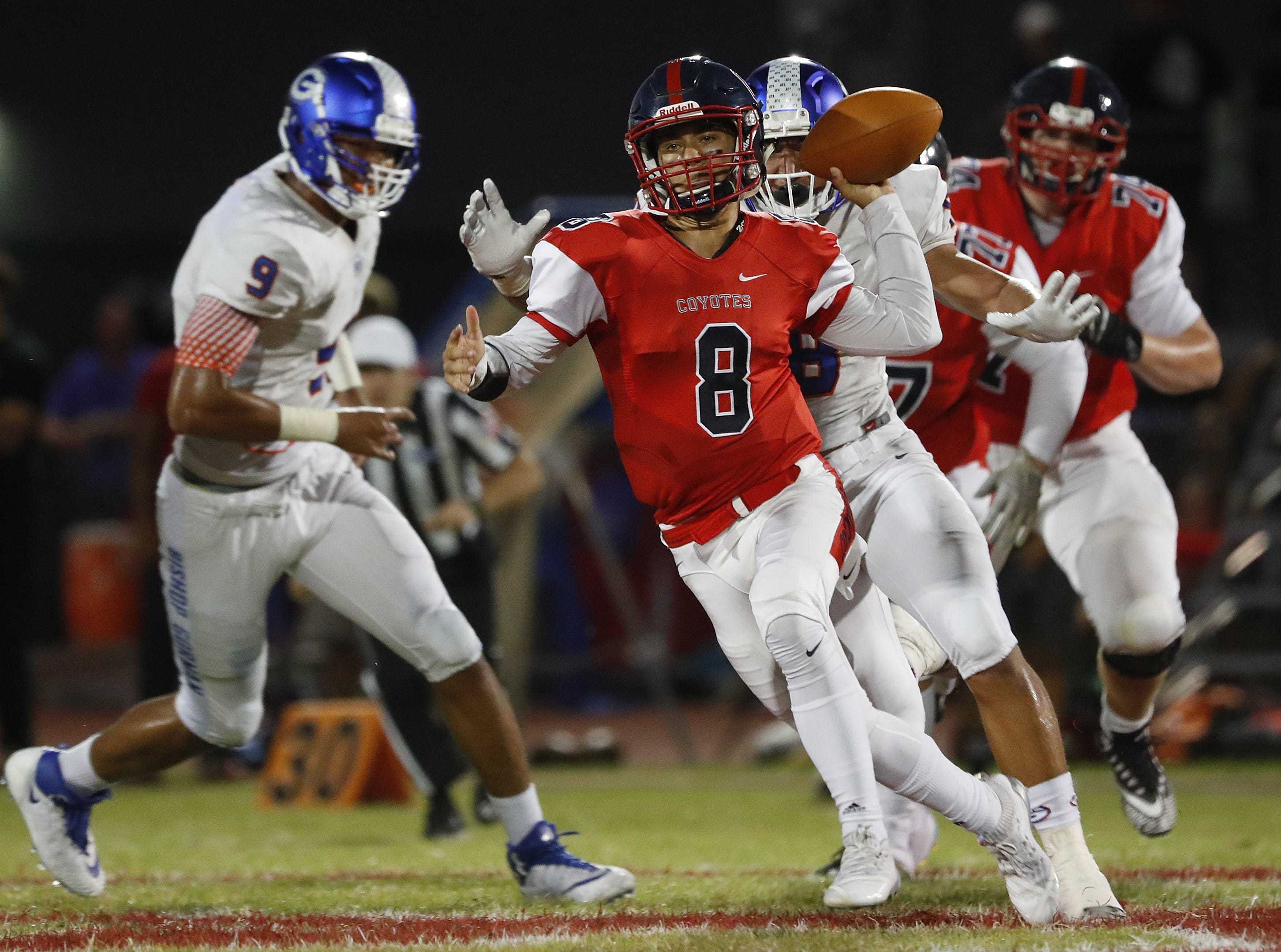 Centennial's Jonathan Morris throws a pass on the run under pressure from Bishop Gorman during a game at Centennial High School in  Peoria, Ariz. on Aug. 31, 2018.