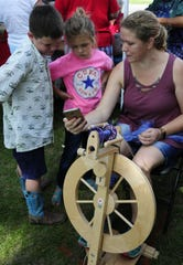 Sophie Derrick talks about spinning yarn with Claude and Lina Sneed at the Algonac Art Fair on Saturday, Sept. 1, 2018.