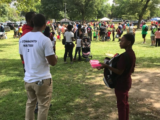 Jazylo Taylor, right, holds his backpack next to his father, L'Quette, and Christopher Grant at the 18th annual Church Picnic Dedicated to God.